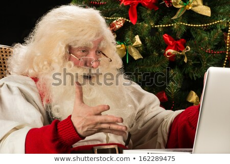 Santa Claus using laptop at home against Christmas Tree and is r Stock photo © HASLOO