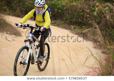 Closeup of woman riding mountain bike outdoors. Stock photo © luckyraccoon