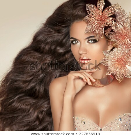 Beautiful brunette model with Long wavy hair and golden makeup.  Stock photo © Victoria_Andreas