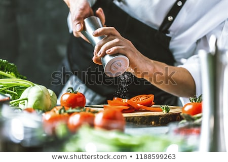 Chef cutting a green cucumber in his kitchen stock photo © master1305
