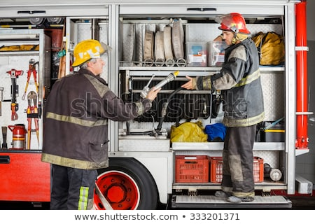 Fire fighter checking the hoses at fire engine Stock photo © Kzenon