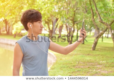 Stock photo: Smiling young asian man listening music and make selfie