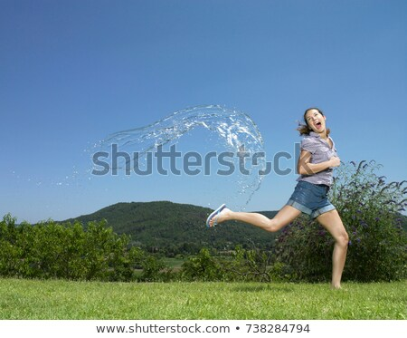 girl running from arc of water stock photo © is2