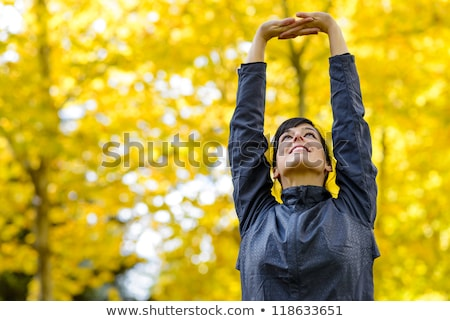 smiling young sportswoman doing stretching exercises stock photo © deandrobot
