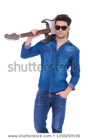 young cool guitarist holding guitar on his shoulder stock photo © feedough