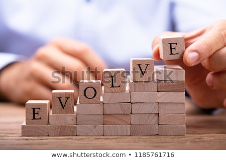 persons hand placing last alphabet of word evolve stock photo © andreypopov