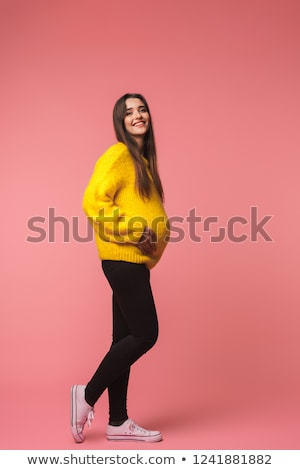 Stock photo: Happy cute young woman posing isolated over pink background using mobile phone listening music.