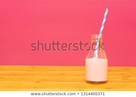 Milk bottle half full with strawberry milkshake with a straw Stock photo © sarahdoow