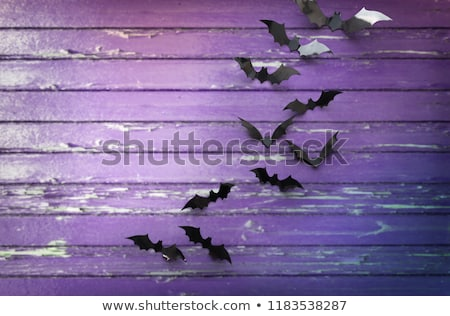 Stock photo: black bats over ultra violet shabby boards