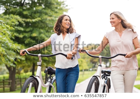 beautiful woman walking on bicycle in the park outdoors foto stock © deandrobot