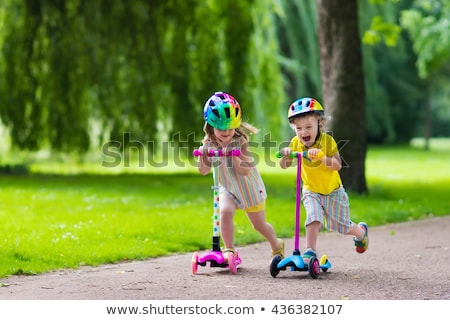 Two girls friends sisters on rollers in park outdoors. Stock photo © deandrobot