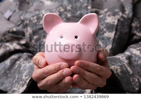 Soldier's Hand Holding Piggy Bank Stock photo © AndreyPopov