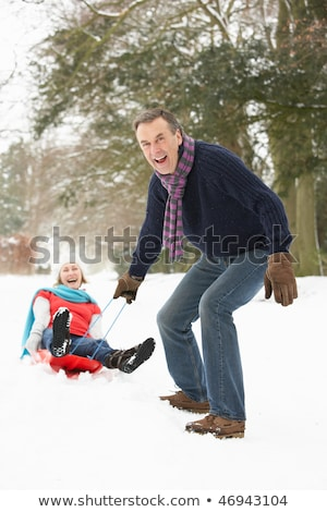 couple sledging through snowy woodland stock photo © monkey_business