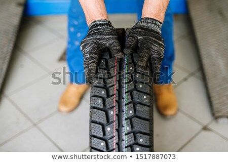 Gloved hands of contemporary technical service worker moving new tyre forwards Stock photo © pressmaster