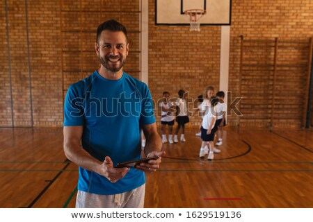 Front view of happy basketball coach using digital tablet at basketball court in school Stock photo © wavebreak_media