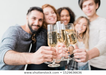 Stock photo: Several flutes with sparkling champagne held by group of joyful young friends