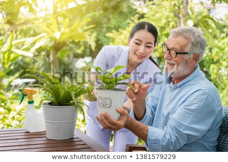 Young man and woman taking care of plants and watering with pot Stock photo © dash