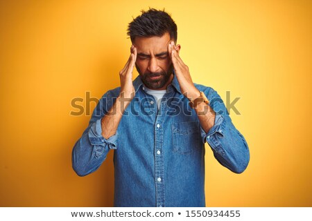 Portrait of young man isolated on yellow background suffering from severe headache, pressing fingers Stock photo © benzoix