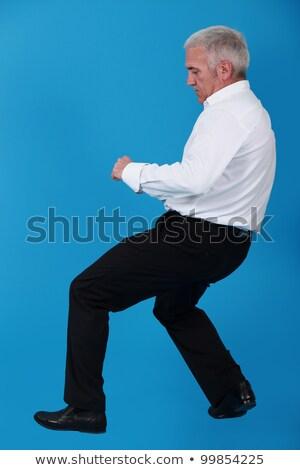 Idős férfi húz láthatatlan tárgy kék Stock fotó © photography33