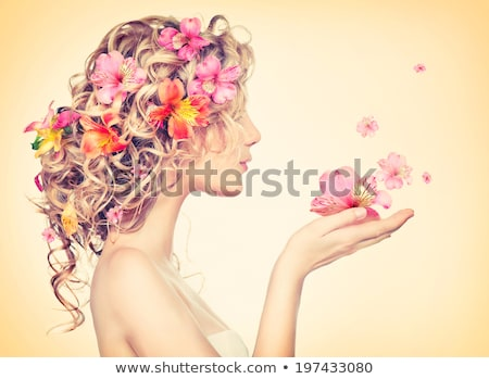 young beautiful woman with flowers in long wavy hair stock photo © rosipro