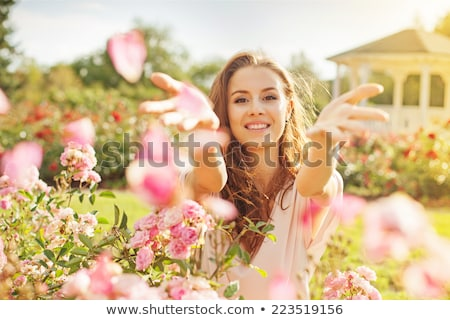 portrait of a cheerful beautiful woman in spring garden stock photo © deandrobot