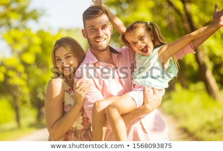 Young happy family in nature with opened arms looking up and breathing fresh air Stock photo © zurijeta