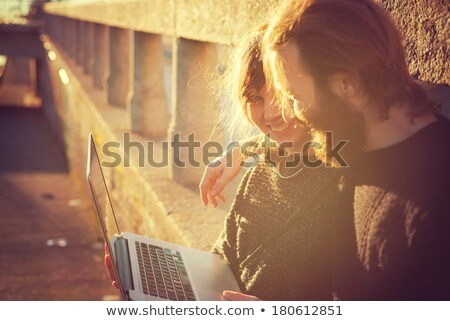 beautiful young blond using laptop outdoors stock photo © lithian