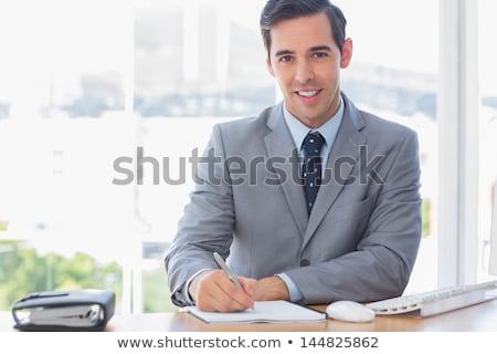 Człowiek zauważa notatnika patrząc kamery Zdjęcia stock © deandrobot