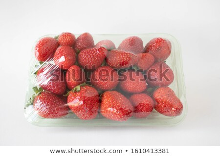 plastic tray container of fresh organic healthy strawberries on stone kitchen table background tray stock photo © denismart