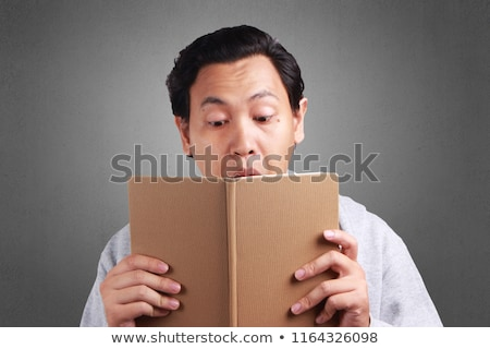 man looking up and wondering with book opened in hand Stock photo © feedough