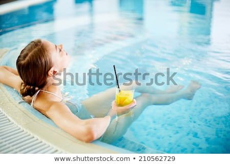 pretty young woman by the glass of the indoor swimming pool at w stock photo © boggy