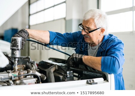 Senior master in workwear and eyeglasses repairing engine of car with drill Stock photo © pressmaster