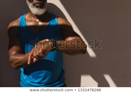 Mid section of senior African American man using smartwatch in the backyard of home Stock photo © wavebreak_media