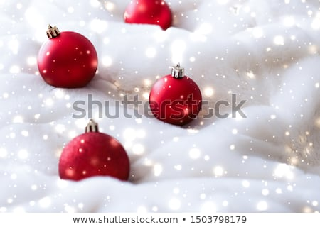 Red Christmas baubles on fluffy fur with snow glitter, luxury wi Stock photo © Anneleven