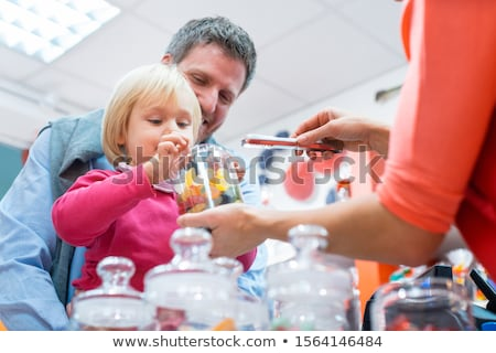 Saleslady for sweet things handing some candy to a kid Stock photo © Kzenon