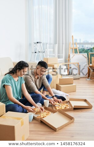 Family couple take break in their new apartment after moving in, lies on floor and surf internet via Stock photo © vkstudio