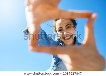 Attractive brunette smiling with hands in air Stock photo © stryjek