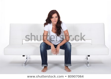 Casually dressed woman sitting on a white modern bed settee Stock photo © photography33