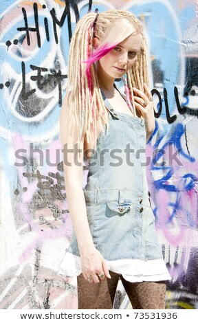 Stock photo: young woman standing at graffitti wall