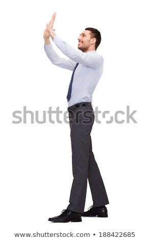smiling businessman pushing up something imaginary Stock photo © dolgachov