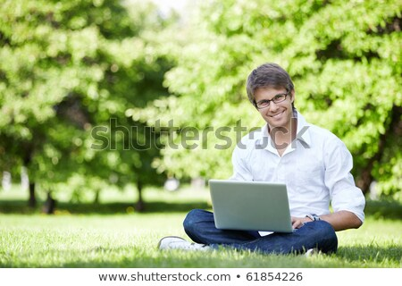 smiling young casual man sitting in a field stock photo © feedough