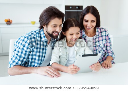 man in checkered shirt using tablet on the kitchen stock photo © deandrobot