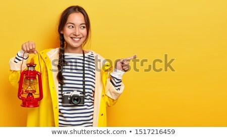 Asian traveler pointing with her forefinger. Stock photo © RAStudio