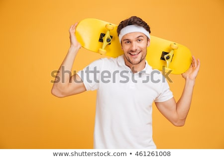 Young happy skateboarder man holding skateboard Stock photo © deandrobot