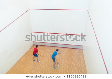 Rear view of two competitive young men playing squash game Stock photo © Kzenon