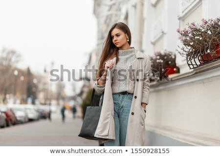A beautiful young girl in a white coat is standing near the shelter and holding a red folder under h Stock photo © Traimak