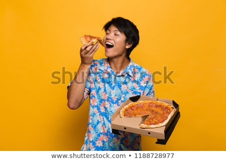 Young asian man standing isolated over yellow background eat pizza. Stock photo © deandrobot
