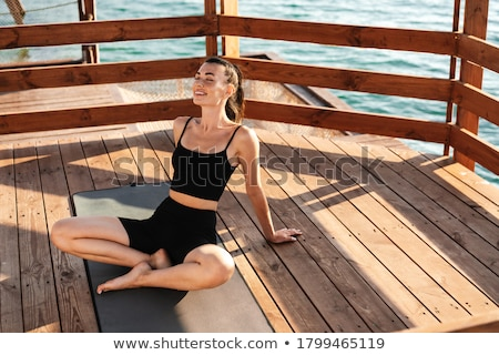 Sports woman sitting on rug outdoors on the beach. Stock photo © deandrobot