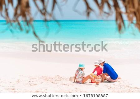 Kid playing on the seashore with shovel and bucket Stock photo © galitskaya