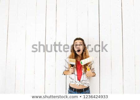 Image of surprised woman 20s holding roller and brush, while pai Stock photo © deandrobot
